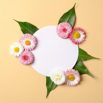 Conceito de férias de primavera. layout criativo feito de flores coloridas com folhas verdes e sobrecarga de cartão de papel em forma de círculo em branco