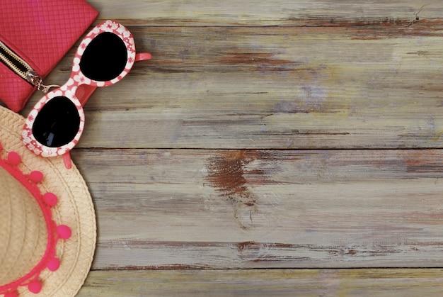 Conceito de férias de verão. chapéu de palha e óculos escuros sobre fundo de madeira.