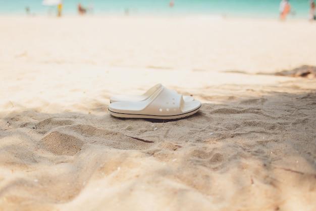 Conceito de férias de verão. chinelos em uma praia arenosa do oceano.