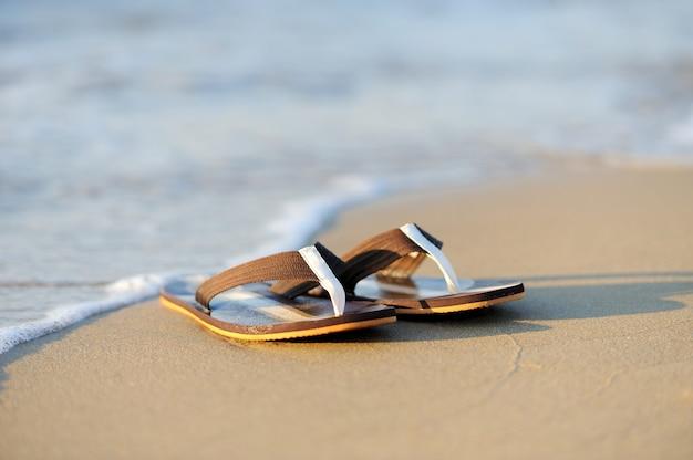 Conceito de férias de verão. chinelos em uma praia de areia do oceano