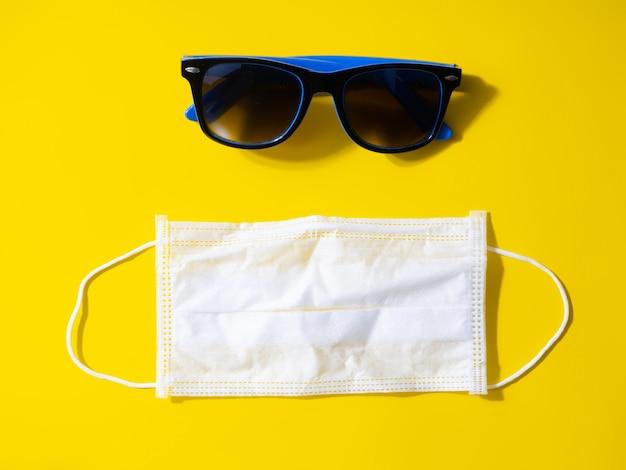 Conceito de férias de verão e viagens nas condições da pandemia covid-19. óculos e máscara em uma mesa amarela. postura plana, cópia espaço.