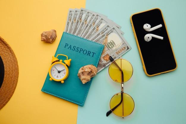 Conceito de férias de verão. óculos de sol, smartphone, chapéu e passaporte com notas de dinheiro na superfície azul amarela