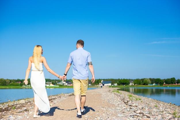 Conceito de férias de verão - vista traseira de casal feliz aproveitando o verão na praia