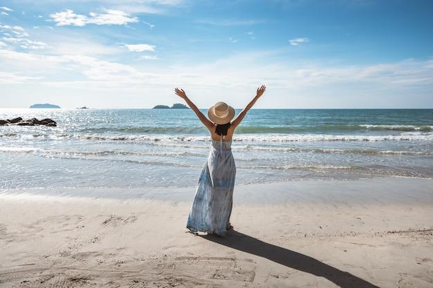 Conceito de férias de viagens de praia de verão, mulher asiática feliz viajante com vestido branco relaxante na praia à noite na tailândia, estilo vintage