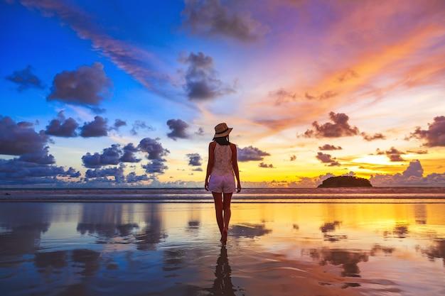 Conceito de férias de viagens de verão. mulher asiática com chapéu relaxando e passeando na praia de kata ao pôr do sol em phuket, tailândia