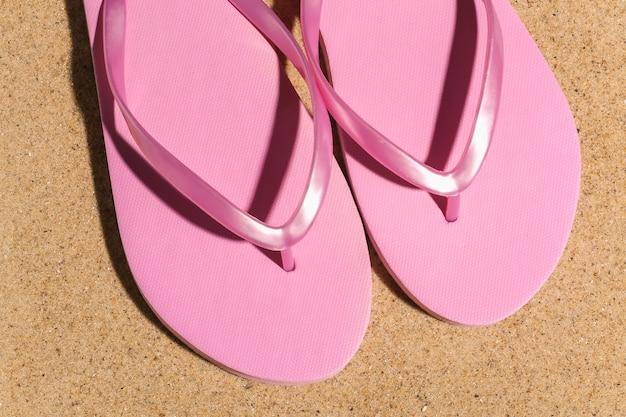 Conceito de férias do verão praia viajar. flip-flops na areia em um dia ensolarado. vista do topo