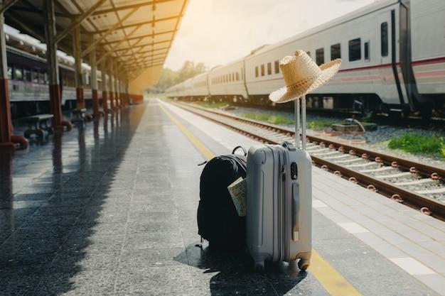 Conceito de férias e viagens. saco de viagem, chapéu de palha e mapa na estação de trem