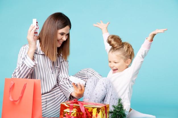 Conceito de férias em família. mãe e filha de pijama com presentes juntos, sentados no chão da sala azul.