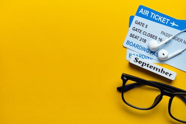 Conceito de férias em setembro com bilhetes de avião em um fundo amarelo.