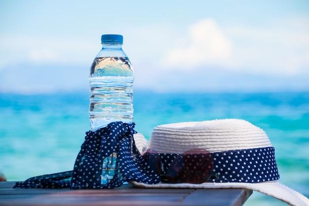 Conceito de férias. essentials na praia do mar. garrafa de água potável, chapéu branco de verão