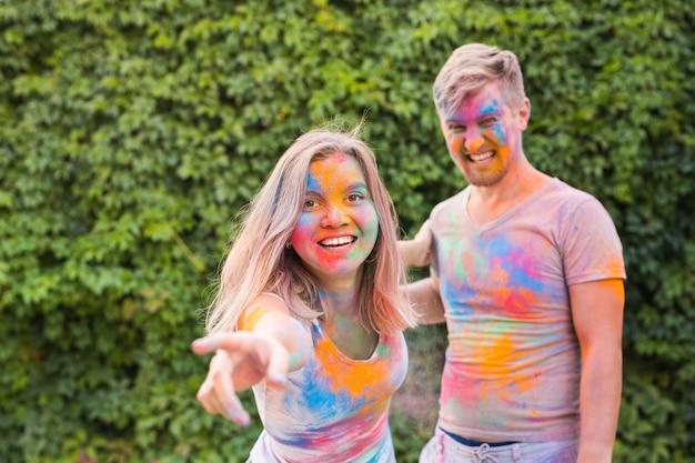 Conceito de férias, feriado e pessoas - casal feliz com pó multicolorido no rosto