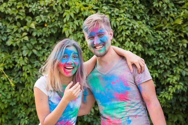 Conceito de férias, feriado e pessoas - sorrindo, mulher e homem posando com pó multicolorido