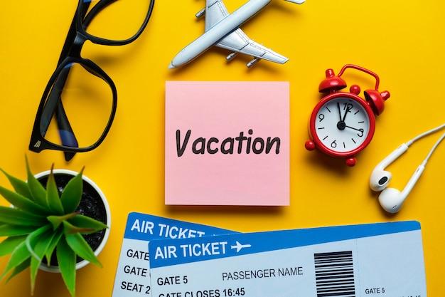 Conceito de férias na etiqueta ao lado de bilhetes e avião com vista superior.