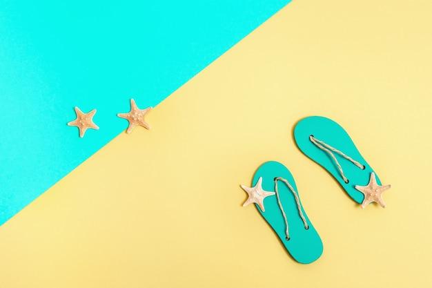 Conceito de férias na praia. chinelos de praia e pequenas estrelas do mar em fundo de papel brilhante.