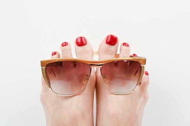 Conceito de férias na praia. pés de óculos em um espaço em branco close-up