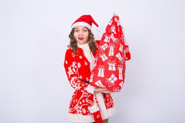 Conceito de férias, natal e presentes - linda mulher fantasiada de papai noel com um grande e pesado saco de presentes.