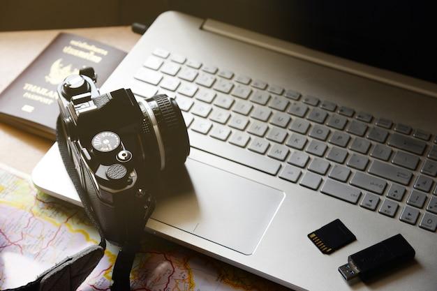 Conceito de férias passaporte câmera flash drive armazenamento mapa notebook computador no fundo da mesa de madeira