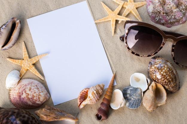 Conceito de férias praia com conchas, seastars e um cartão em branco