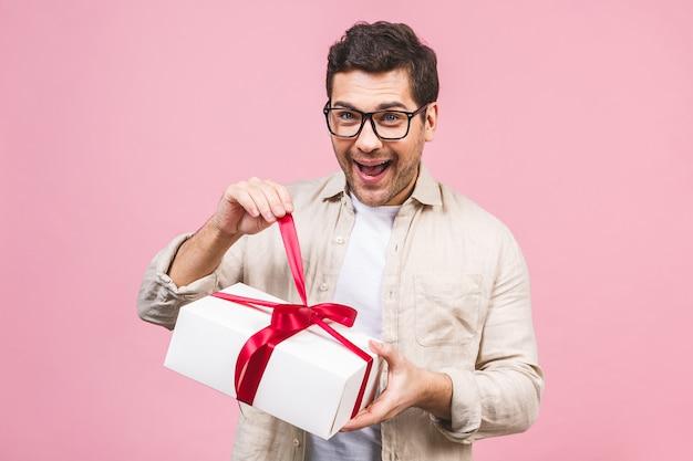 Conceito de férias. retrato de uma caixa de presente da abertura do homem novo isolada sobre a parede cor-de-rosa.