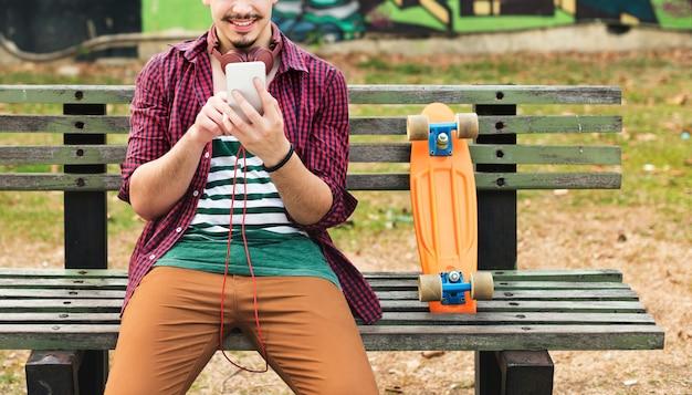Conceito de férias skateboarding sentado parque de relaxamento