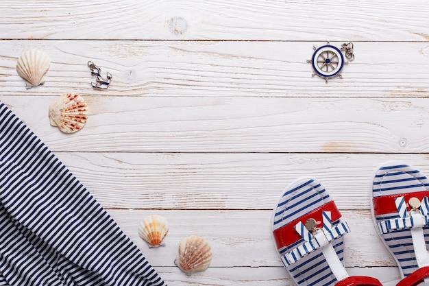 Conceito de férias viagem com sandálias, conchas e camiseta listrada. vista superior com espaço para texto