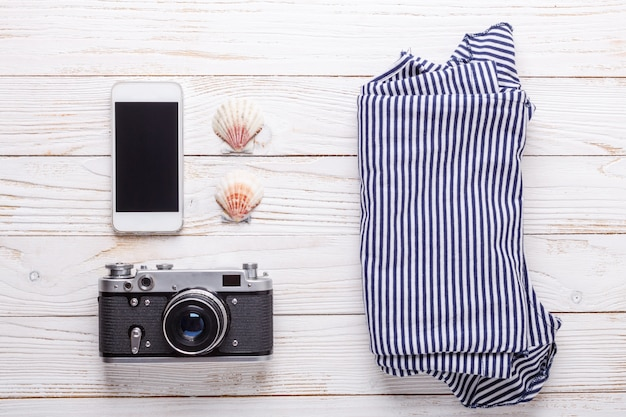Conceito de férias viagens com câmera, smartphone, conchas e camiseta listrada.