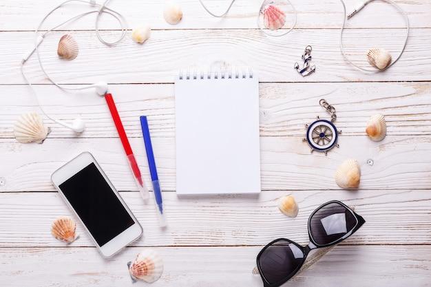 Conceito de férias viagens com fones de ouvido, óculos de sol, smartphone, conchas, caderno.