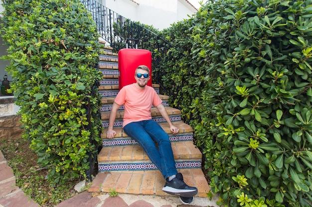Conceito de férias, viagens e bagagem - jovem com mala sentado na escada.