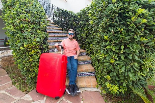 Conceito de férias, viagens e pessoas. homem com mala de viagem vermelha sentado na escada de sua casa.
