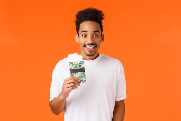 Conceito de férias, voo e viagem. bonito homem afro-americano feliz segurando o passaporte