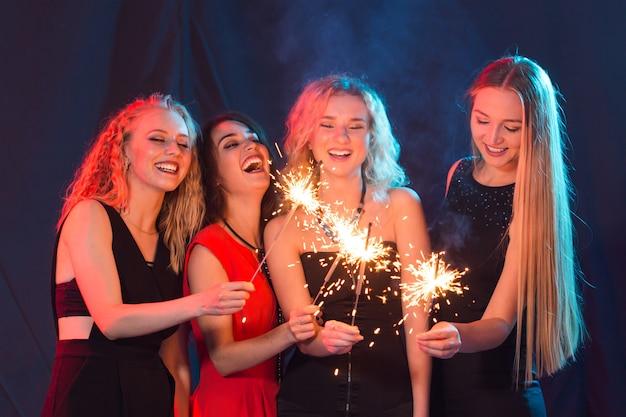 Conceito de festa, ano novo e feriados de aniversário - grupo de amigas comemorando segurando estrelinhas.