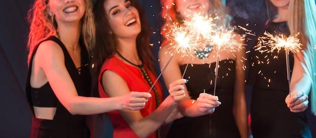Conceito de festa, celebração e feriados de ano novo - jovens mulheres alegres segurando estrelinhas acesas.