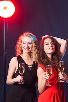 Conceito de festa de aniversário, ano novo e feriados - amigas alegres comemorando com taças de champanhe, close-up
