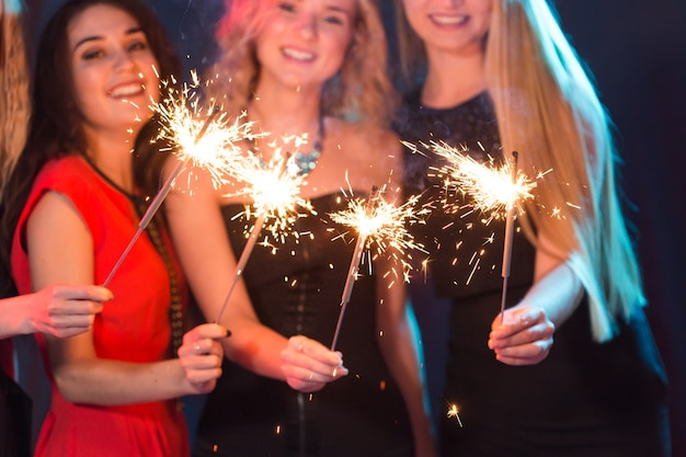Conceito de festa de aniversário, ano novo e feriados - grupo de amigas comemorando segurando um close de estrelinhas