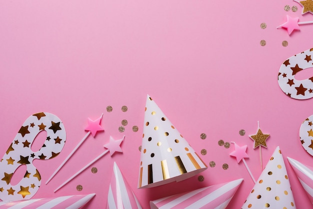 Conceito de festa de aniversário. chapéus de festa, máscaras e velas de aniversário no fundo rosa. vista de cima para baixo com espaço de cópia