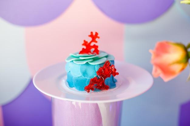 Conceito de festa de aniversário. tabela para crianças com os cupcakes com parte superior azul e vermelha e artigos decorados em cores azuis e roxas brilhantes. temporada de verão deliciosa na festa.