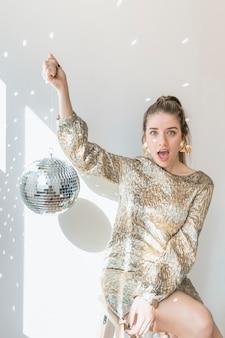Conceito de festa de ano novo com garota segurando bola de discoteca