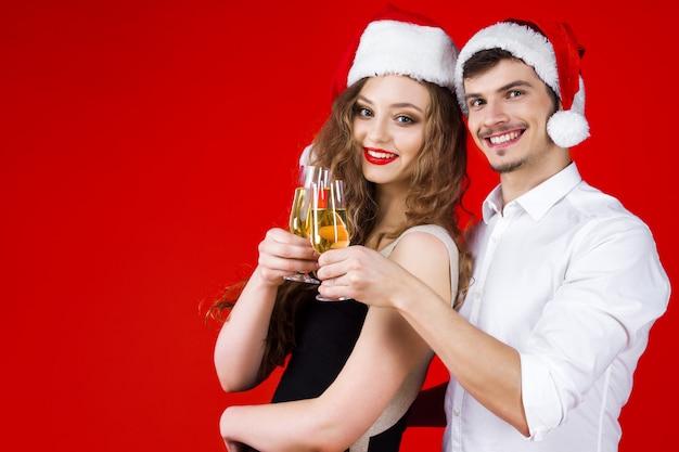 Conceito de festa de ano novo feliz diversão sorrindo amigos casal hipster vestindo fantasia de carnaval de conto de fadas papai noel chapéu de natal segurando um brinde de champanhe de vidro comemorando as férias de inverno