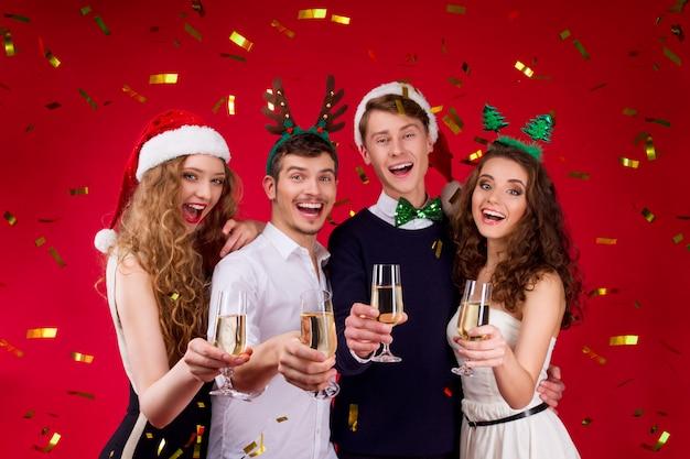 Conceito de festa de ano novo feliz diversão sorrindo amigos companhia vestindo traje de carnaval de conto de fadas santa deer christmas tree hat segurando vidro champanhe comemorando férias de inverno confetes