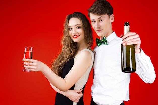 Conceito de festa de ano novo feliz diversão sorrindo amigos descolados comemorando o inverno férias de natal vestindo traje de carnaval de conto de fadas gravata borboleta segurando uma garrafa de champanhe de vidro felicidades