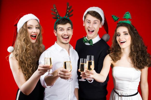 Conceito de festa de ano novo feliz diversão sorrindo amigos hipster companhia vestindo traje de carnaval de conto de fadas papai noel veado chapéu de árvore de natal segurando vidro champanhe comemorando as férias de inverno