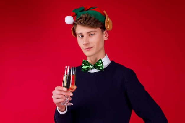 Conceito de festa de ano novo feliz diversão sorrindo charmoso hipster homem macho cara comemorando inverno férias de natal usando chapéu de duende orelhas verde segurando champanhe vidro brinde