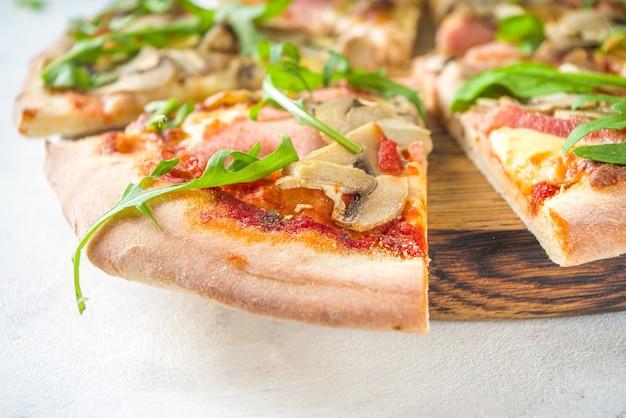Conceito de festa de pizza. conjunto de pizzas com recheios diversos, pedaços de pizza diferentes, taças e garrafa com vinho.