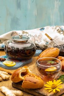 Conceito de festa do chá com bolos doces em copo de vidro de mesa de madeira e foco seletivo de bule