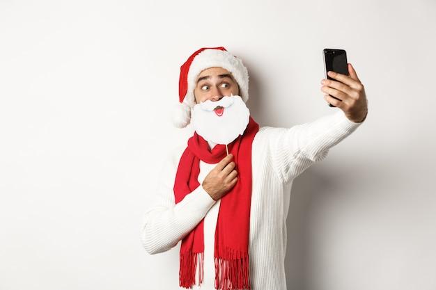 Conceito de festa e celebração de natal. jovem tirando selfie com máscara e chapéu de papai noel com barba branca engraçada, posando para foto no celular, plano de fundo do estúdio
