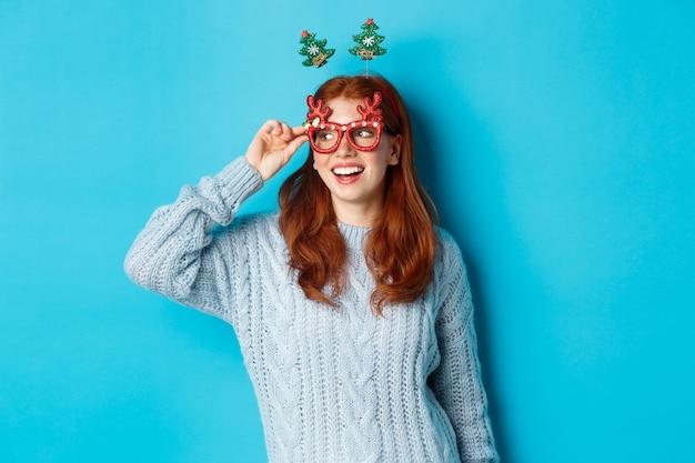 Conceito de festa e celebração de natal. menina adolescente ruiva fofa comemorando o ano novo, usando bandana de árvore de natal e óculos engraçados, olhando para a esquerda divertido, fundo azul.