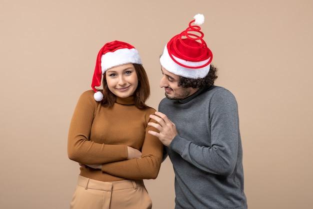 Conceito de festa e clima de ano novo - jovem casal adorável e animado usando chapéu de papai noel em estoque cinza