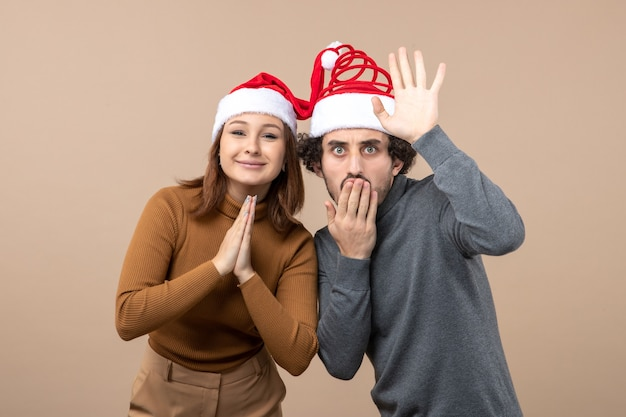 Conceito de festa e clima de ano novo - jovem casal adorável e animado usando chapéus de papai noel na cor cinza