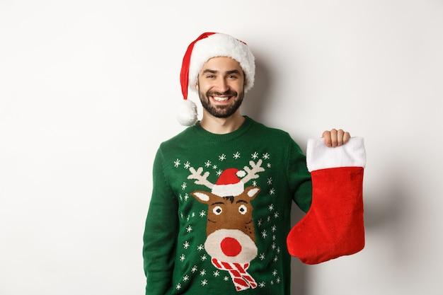 Conceito de festa e feriados de natal. homem feliz com chapéu de papai noel trazendo presentes na meia de natal e sorrindo, em pé sobre um fundo branco.