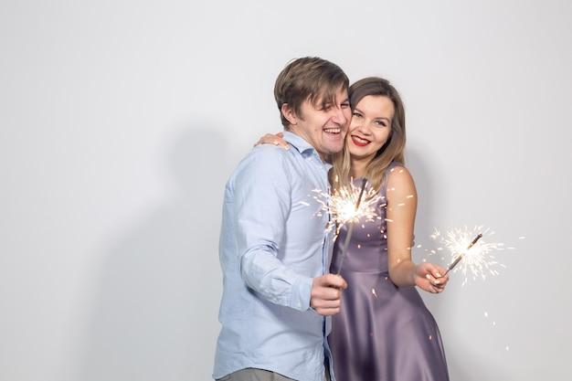 Conceito de festa, família e feriados - jovem casal comemorando seu aniversário com estrelinhas na parede branca.